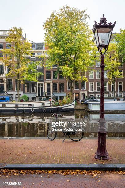 street lamp and bicycle next to a canal in amsterdam, holland - amsterdam stock pictures, royalty-free photos & images