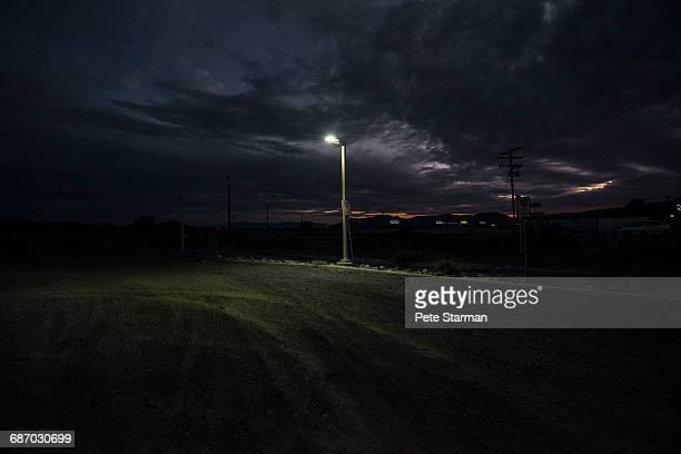 street lamp at edge of dirt parking lot. - poste imagens e fotografias de stock