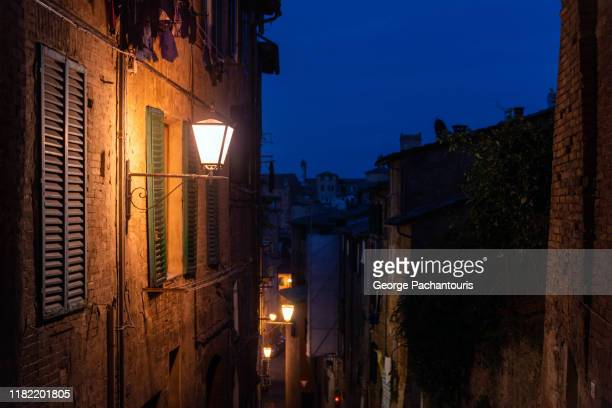 street lamp in the old town of siena, italy at night - siena italy stock pictures, royalty-free photos & images