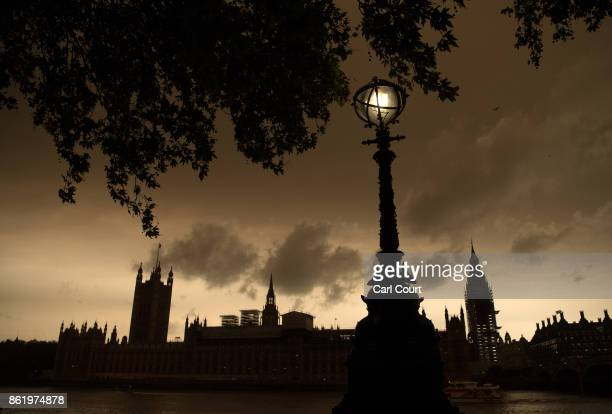 A street lamp is lit opposite the Houses of Parliament during a reddish sky caused by remnants of Hurricane Ophelia dragging in dust from the Sahara...