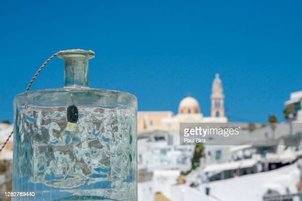 street lamp with st john the baptist cathedral in fira in the background - greek orthodoxy stock pictures, royalty-free photos & images