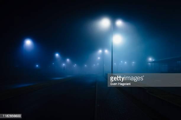 street lamps illuminated over foggy, vacant road - mystery stock pictures, royalty-free photos & images