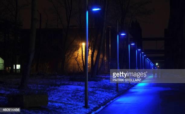 Street lamps light up a street at the Zeche Zollverein coal mining plant in Essen western Germany on December 30 2014 Mining activities at Zeche...