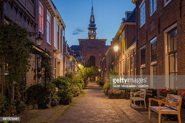street leading towards church in city at dusk - haarlem stock photos and pictures