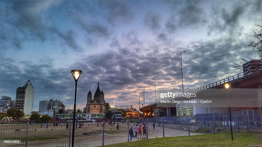 Street Light And Buildings By Bridge Against Cloudy Sky At Dusk : Stock Photo