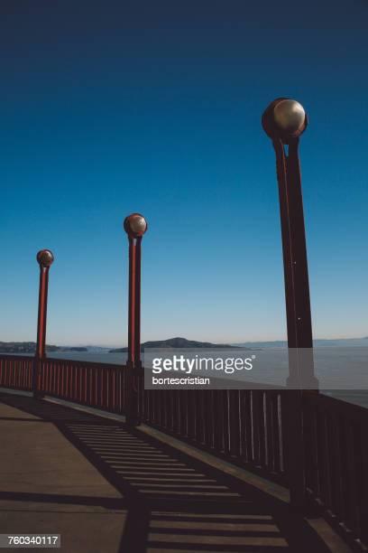 street light by sea against clear blue sky - bortes stockfoto's en -beelden