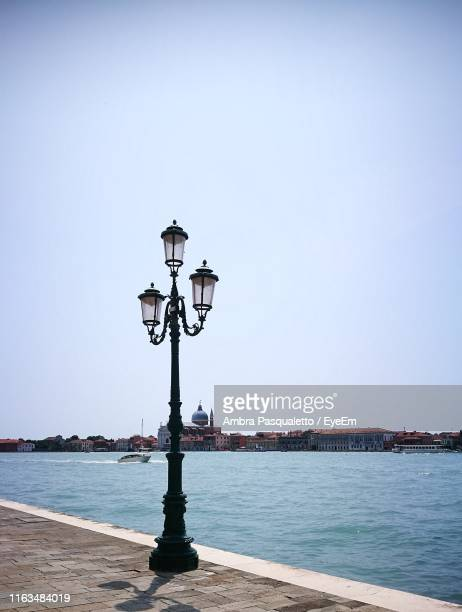 street light by sea against clear sky - ガス燈 ストックフォトと画像