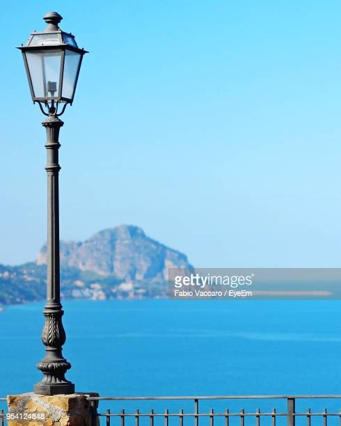 street light by sea against clear sky - luce stradale foto e immagini stock
