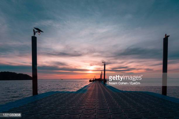 street light by sea against sky during sunset - noam cohen stock pictures, royalty-free photos & images