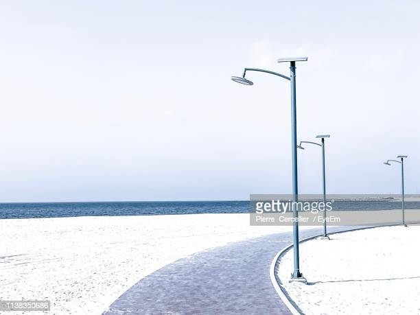 street light by sea against sky during winter - gulf countries stock pictures, royalty-free photos & images