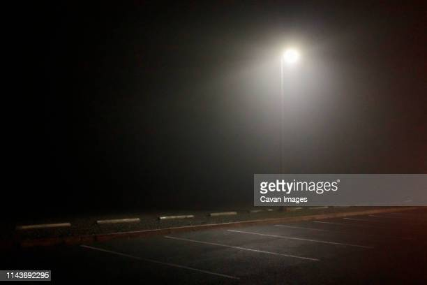 street light illuminating empty foggy parking lot. - empty lot night stock pictures, royalty-free photos & images