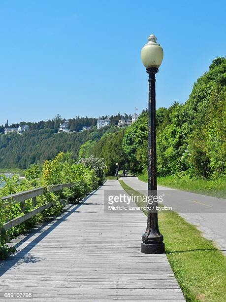 street light on boardwalk by road against clear sky - mackinac island stock pictures, royalty-free photos & images