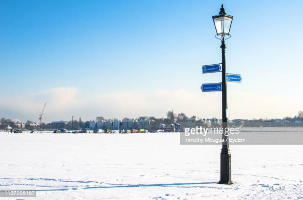street light on snow covered field against blue sky - luce stradale foto e immagini stock