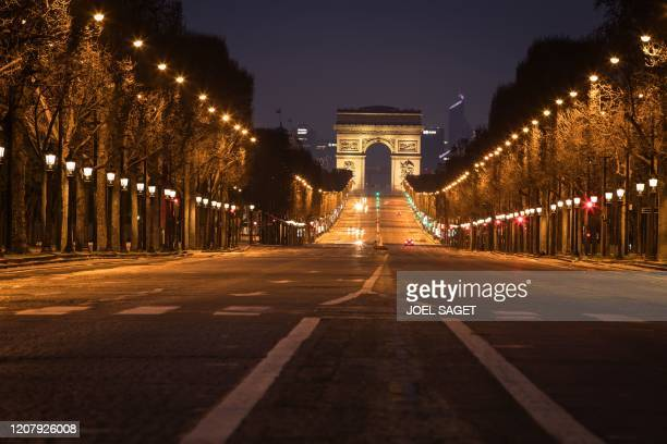 Street lights illuminate a deserted Champs Elysees leading to the Arc de Triumph monument in central Paris on March 21 as a strict lockdown is in...
