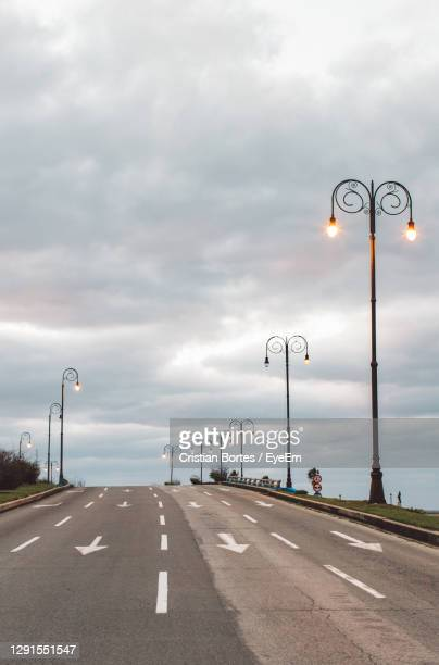street lights on road against cloudy sky - bortes stock pictures, royalty-free photos & images