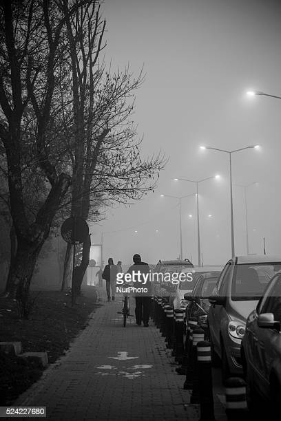 Street lights penetrate a deep fog in Bucharest where winter is harsh for thousands of minors and young adults living in Bucharest's vast system of...