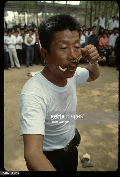 A street magician has pushed a snake up his nose and managed to make it come out his mouth He passes a hat to collect money from an audience gathered...