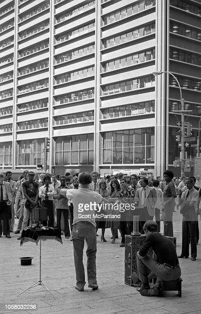 A street magician performs for a crowd in lower Manhattan New York New York September 1980 Visible in the background is the US Steel Building