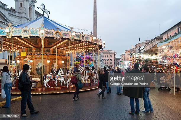 A street market and a carousel in Piazza Navona in downtown area decorated with Christmas lights on December 10 2010 in Rome Italy
