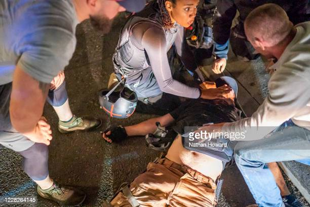 Street medics and protesters help to treat a man who was shot near a ProTrump rally on August 29 2020 in Portland Oregon Far left counterprotesters...