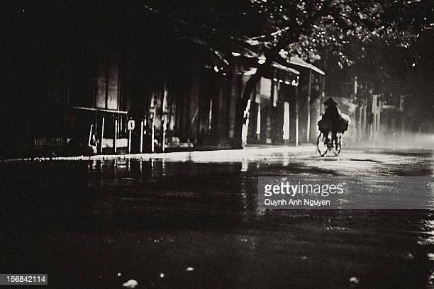 Street merchant riding bicycle in a rainy night