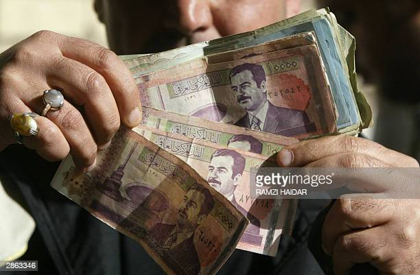 A street money exchange trader displays Iraqi dinar notes with the face of ousted dictator Saddam Hussein in Baghdad 13 January 2004 two days before...