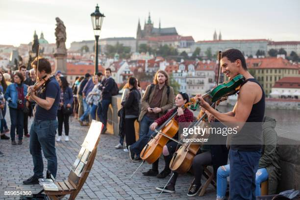 street music band performing in prague - charles bridge stock photos and pictures