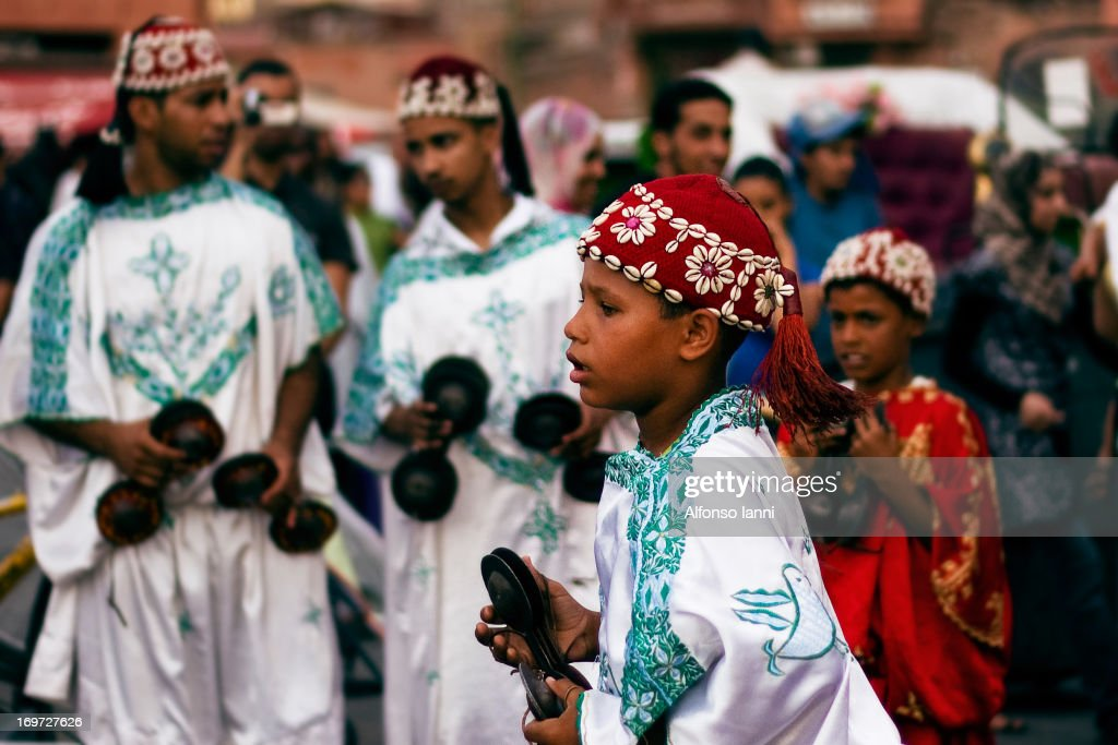 CONTENT] Street musicans on place Djaama el-Fna in Marrakech (Morocco-North Africa). Moroccan Boy performing a traditional dance with Gnawa music.