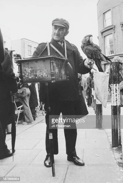 A street musician holding a parrot plays the hurdygurdy in a crowded Portobello Market London 1974