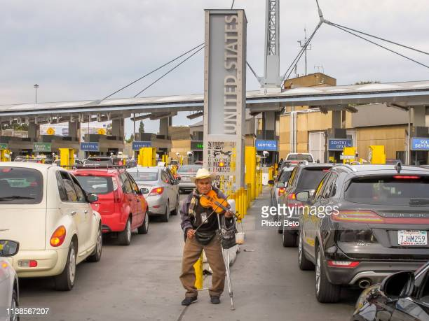 a street musician in front of the us-mexico border station of san ysidro in tijuana - crossing sign stock pictures, royalty-free photos & images