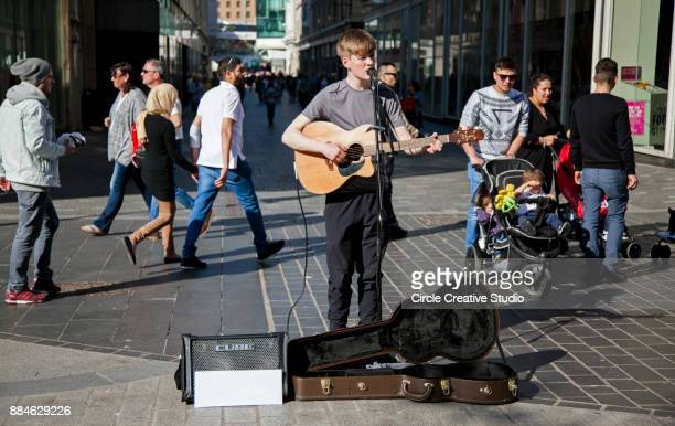 street musician is playing guitar outdoor in liverpool,uk - plucking an instrument stock pictures, royalty-free photos & images