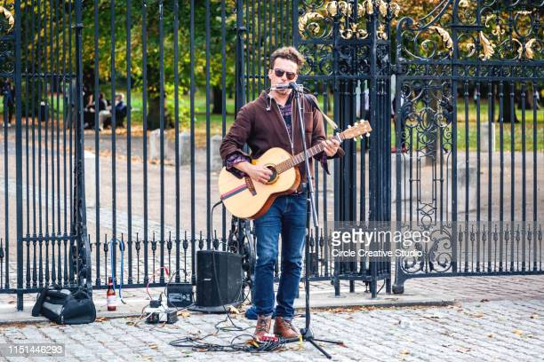 street musician is playing guitar outdoor in london uk - guitarist stock pictures, royalty-free photos & images