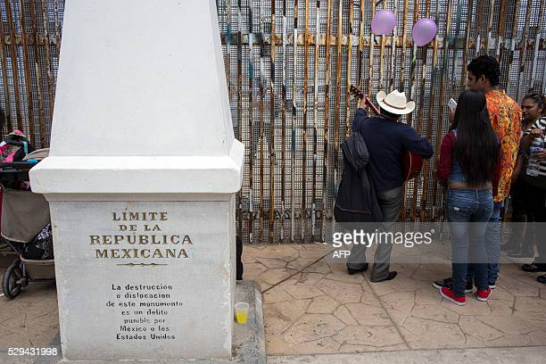 A street musician performs for the families gathering along the fence during the Binational Mothers' Day celebration on the Mexican side of the...