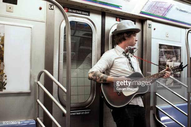 street musician playing guitar in subway train - musician stock pictures, royalty-free photos & images