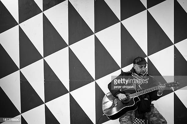 CONTENT] Street musician playing guitar infront of a patterned wall