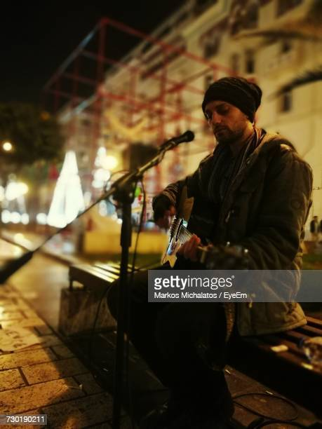 Street Musician Playing Guitar While Sitting On Bench In City At Night
