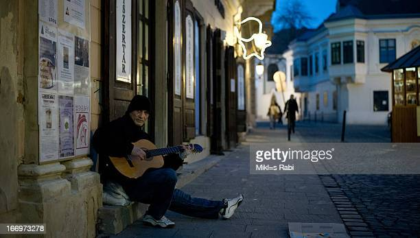 CONTENT] Street musician playing in a guitar