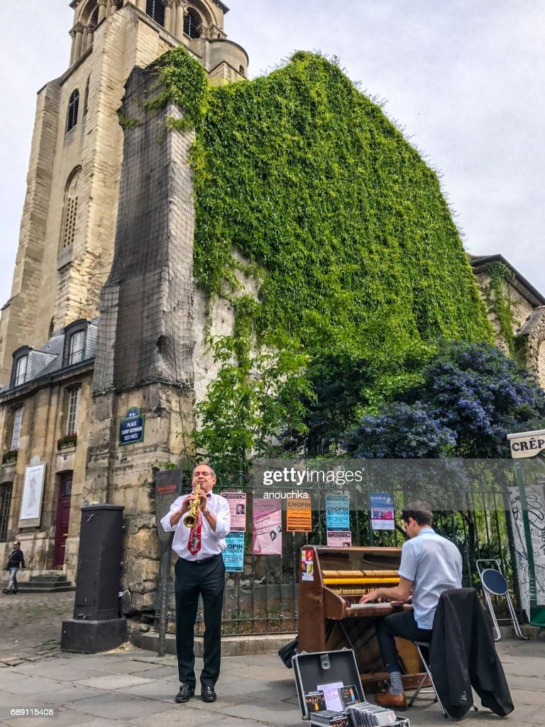 Street Musician playing music near Saint Germain des pres Church, Paris, France : Stock Photo