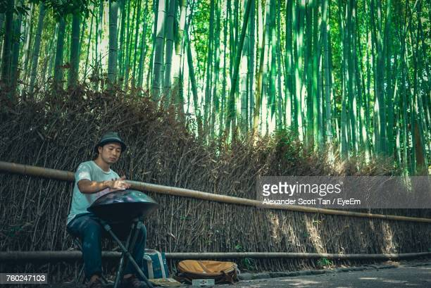 street musician playing music while sitting against fence - bamboo instrument stock photos and pictures