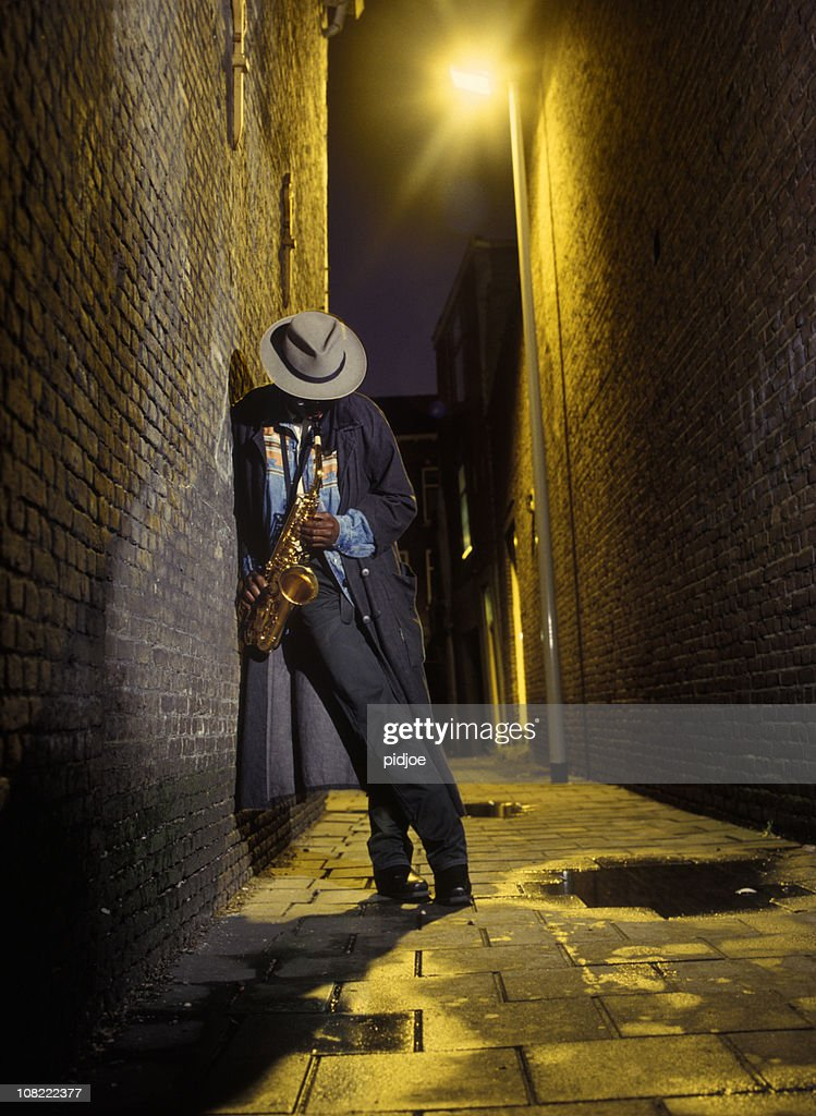 street musician playing saxophone in alley : Stock Photo