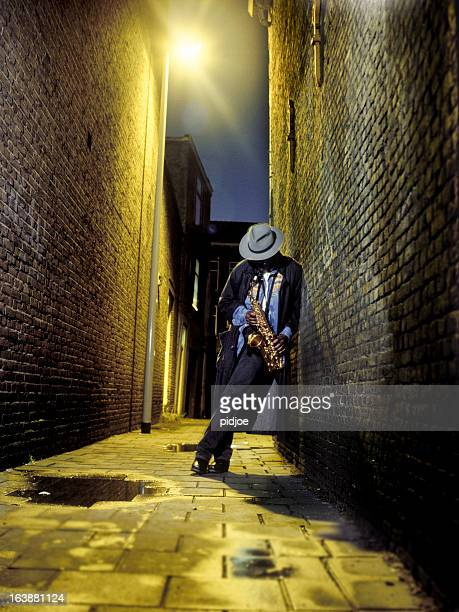 street musician playing saxophone in alley