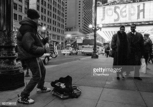 Street musician playing the saxophone in front of Chicago Theater (1996)