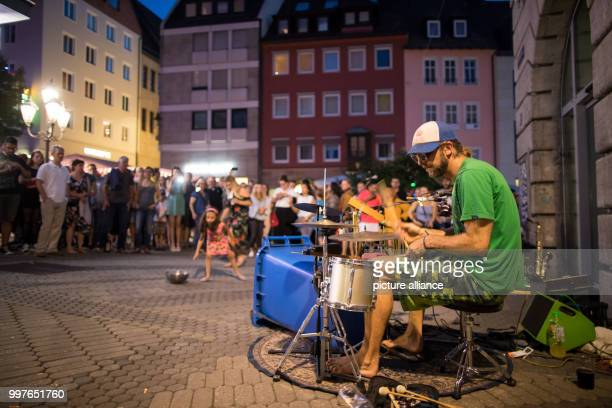 A street musician plays a drumset made of trash cans at the 'Nuernberger Bardentreffen' in Nuremberg Germany 29 July 2017 The programme of the free...