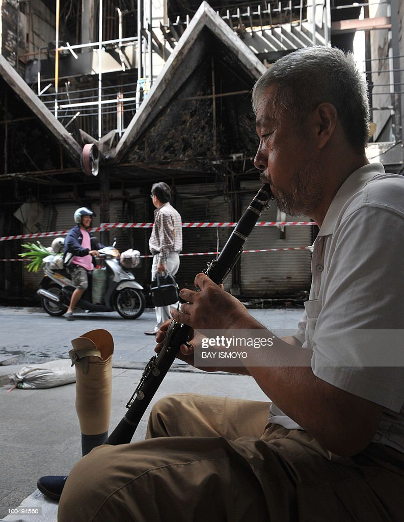 A street musician plays a flute in downtown Bangkok on May 25, 2010. AFP PHOTO / Bay ISMOYO