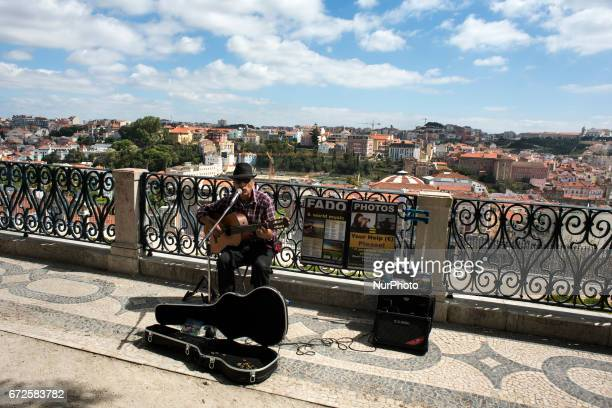 A street musician plays fados in the viewpoint of Sao Pedro Alcantara with the city of Lisbon in the background