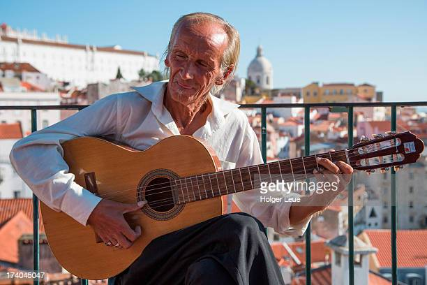 Street musician plays guitar and sings Fado