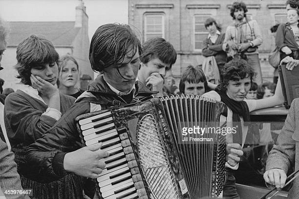 A street musician plays the accordion for an audience Ireland 1981