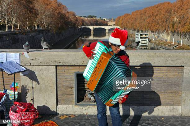 A street musician wearing a Christmas cap plays the accordion on the Ponte Sisto bridge over in the River Tiber on a warm Autumn morning on December...