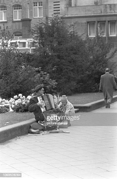 A street musician with dog and accordion plays music on 26 March 1963 in Dusseldorf and enjoys great popularity at least with this little girl |...