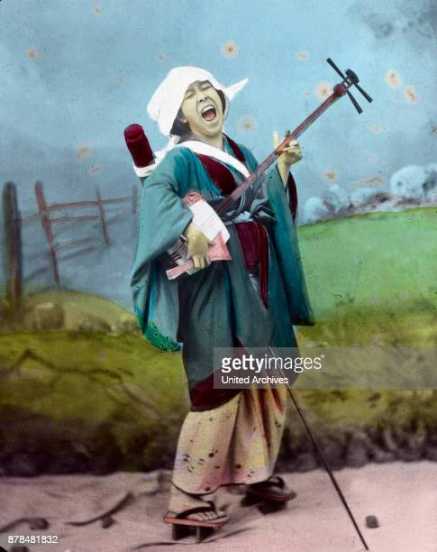 A street musician with her instrument the shamisen